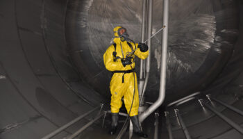 man in chemical suit inside  cargo tank on deck of chemical tanker for cleaning operation